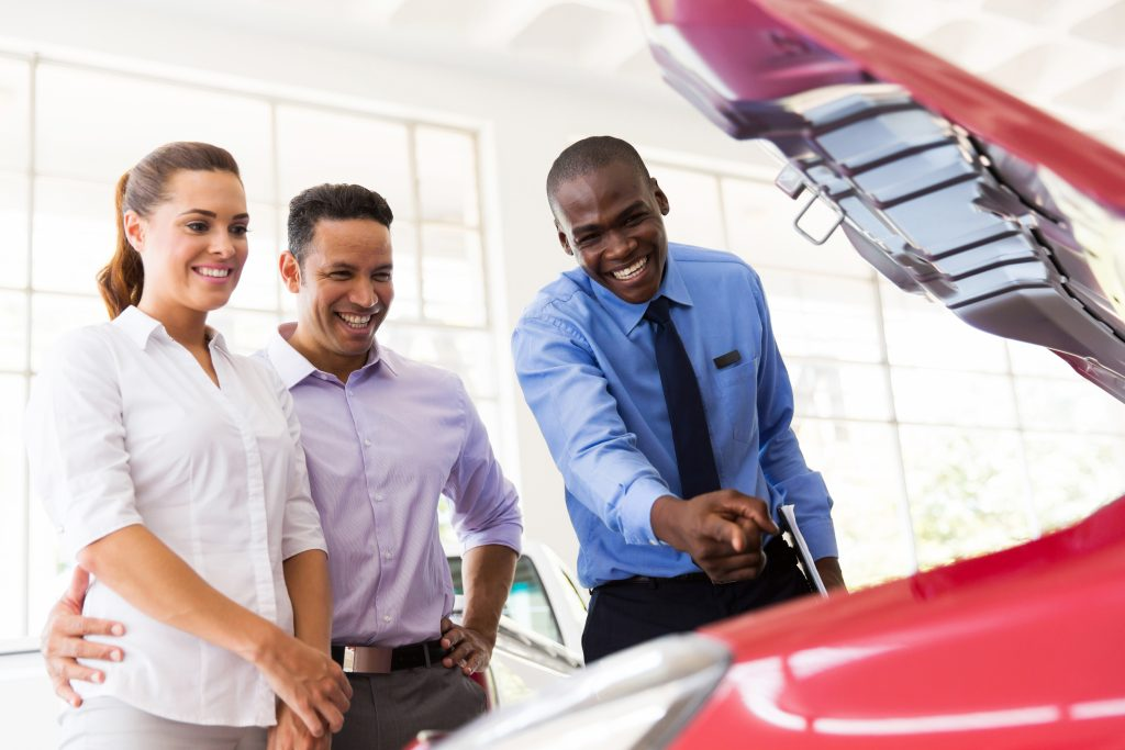happy african car salesman showing car engine to customers
